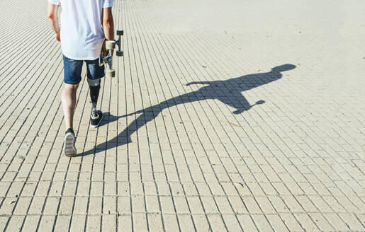 Young man with leg prosthesis walking and holding skateboard - JCMF00226