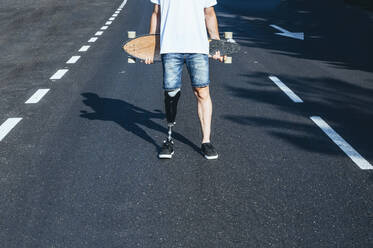 Young man with leg prosthesis holding skateboard on a road - JCMF00229