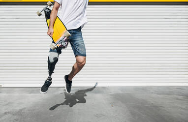 Young man with leg prosthesis holding skateboard and jumping - JCMF00238