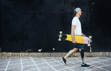 Young man with leg prosthesis holding skateboard passing a wall - JCMF00241