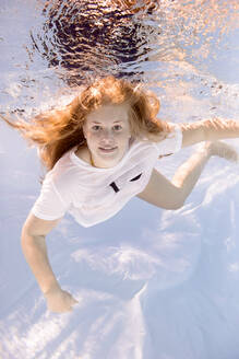 Portrait of teenage girl wearing t-shirt diving under water - STBF00394