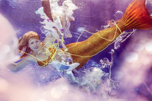 junge Frau in einem Meerjungfrauenkostüm gefangen in Müll, Plastikmüll, Unterwasser, schwimmen, Pool, Schwimmbad, Vilsbiburg, Bayern, Deutschland - STBF00403
