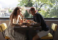Young couple in a coffee shop looking at smartphone during breakfast, Lecco, Italy - MCVF00038