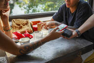 Young woman paying bill with smartphone at coffee shop - MCVF00044