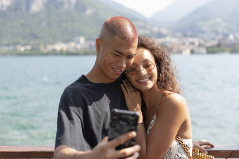 Portrait of happy young couple taking selfie in front of Lake Como, Lecco, Italy - MCVF00047