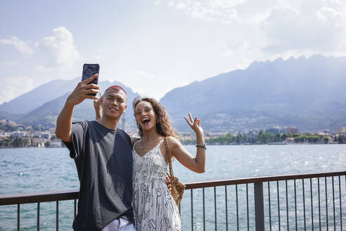 Portrait of young couple taking selfie in front of Lake Como, Lecco, Italy - MCVF00050