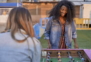 Portrait of happy young woman playing table football with her friend - VEGF00722