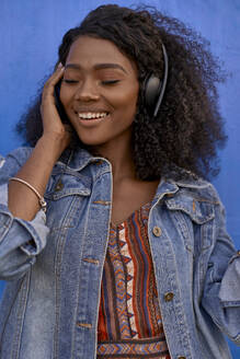 Portrait of smiling young woman listening music with headphones - VEGF00725