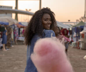 Portrait of happy young woman with pink candyfloss on street market - VEGF00728