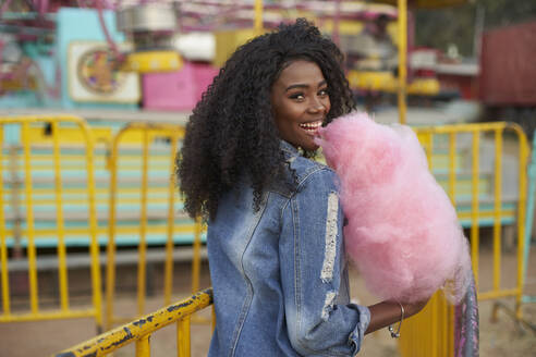 Portrait of happy young woman with pink candyfloss at fair - VEGF00731