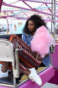 Portrait of young woman with pink candyfloss at fair - VEGF00734