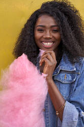 Portrait of happy young woman with pink candyfloss - VEGF00737