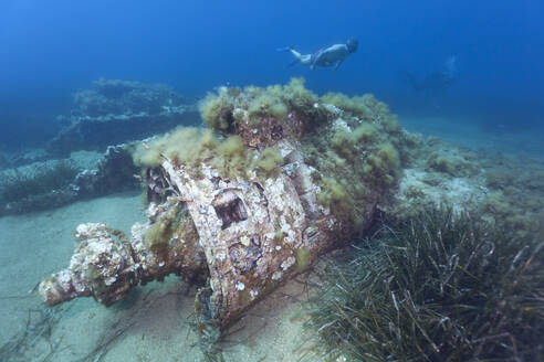 Propeller of sunken airplane wreck with scuba diver swimming in background - ZC00814