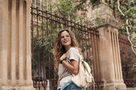Beautiful young woman with curly hair and glasses in the city - LOTF00074