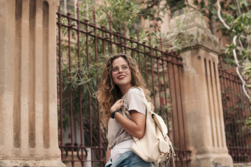 Beautiful teenager with blonde curly hair wearing glasses and holding a bag. Palma de Mallorca, Balearic Islands, Spain. - LOTF00074