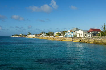 Colonial houses in front of beach against blue sky during sunny day, Cockburn town, Grand Turk - RUNF03227
