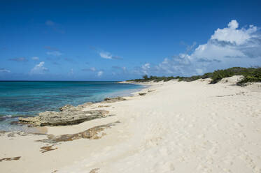 Scenic view of Norman Saunders beach against blue sky at Grand Turk, Turks And Caicos Islands - RUNF03233