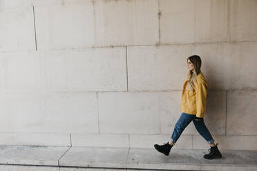 Walking young woman wearing yellow jacket - LHPF00972