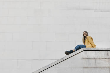 Smiling young woman wearing yellow jacket sitting on a wall - LHPF00975