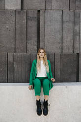 Blond young woman wearing green pantsuit sitting on a wall, Vienna, Austria - LHPF00978