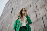 Portrait of laughing young woman wearing green pantsuit, Vienna, Austria - LHPF00981