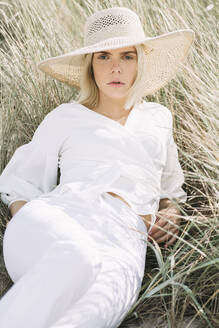 Portrait of blond young woman lying in beach dunes wearing white clothes and summer hat - JESF00334