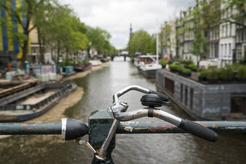 Netherlands, Amsterdam, Handlebar of bicycle parked along railing of canal bridge - XCF00237