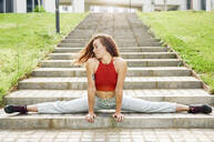 Young woman doing the splits on outdoor stairs - JSMF01270