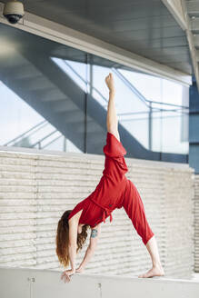 Sporty young woman doing acrobatics on a concrete wall - JSMF01285