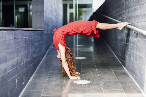 Sporty young woman doing acrobatics at a passageway - JSMF01288