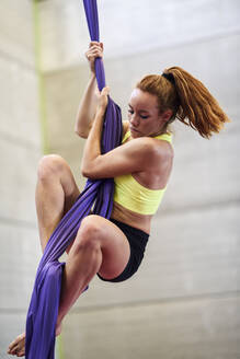 Young woman doing aerial silk in an exercise room - JSMF01300