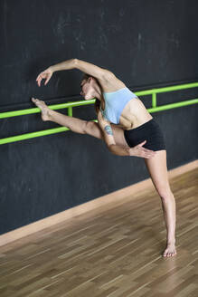 Sporty young woman exercising at barre - JSMF01309