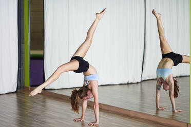 Sporty young woman doing a handstand in exercise room - JSMF01312