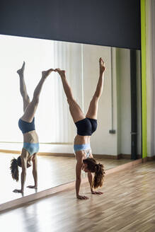 Sporty young woman doing a handstand in exercise room - JSMF01315