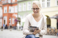 Portrait of young woman using tablet in the city - JESF00359