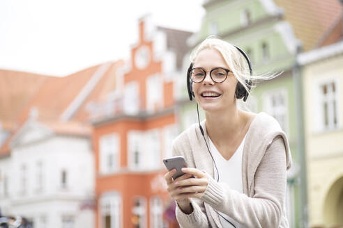 Portrait of blond woman using smartphone and headphones - JESF00362
