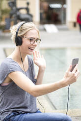Portrait of blond woman using smartphone and headphones, video chatting - JESF00365