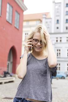 Junge Frau mit Brille telefoniert in der Innenstadt und lächelt dabei; Deutschland, Mecklenburg-Vorpommern, Greifswald - JESF00371