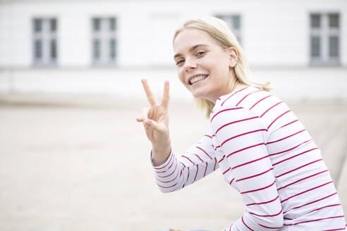 Junge blonde Frau im gestreiften T-Shirt zeigt ein Peace-Zeichen in die Kamera und lacht dabei; Deutschland, Mecklenburg-Vorpommern, Greifswald - JESF00377
