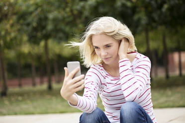 Portrait of blond woman using smartphone and taking a selfie - JESF00380