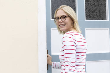 Young blond woman opening entrance door - JESF00383