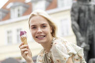 Portrait of young blond woman eating icecream - JESF00386