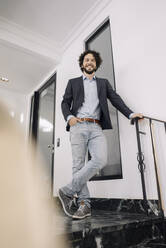 Confident businessman standing on office floor - KNSF06590