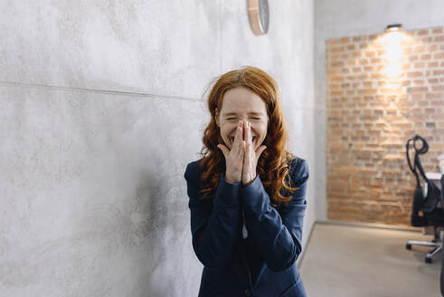 Laughing redheaded businesswoman in office - KNSF06593