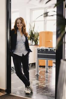 Portrait of smiling redheaded businesswoman in office - KNSF06599