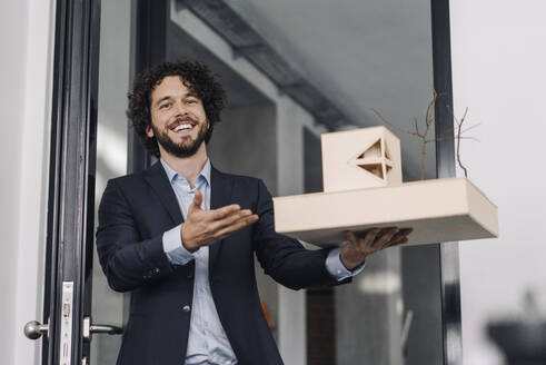 Happy architect in office holding architectural model - KNSF06602