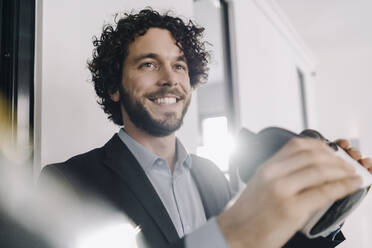 Portrait of smiling businessman holding VR glasses in office - KNSF06605