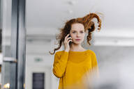 Woman with windswept hair on the phone in office - KNSF06608