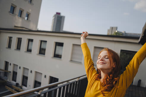 Smiling redheaded woman stretching on roof terrace - KNSF06617