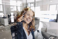 Happy redheaded businesswoman on the phone in office - KNSF06635